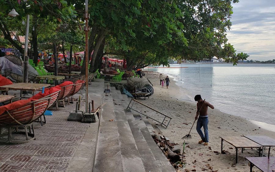 Vendors sweep leaves from the beach and restaurant seating area at Sihanoukville's Independence Beach on November 30, 2020. (Danielle Keeton-Olsen/VOD)