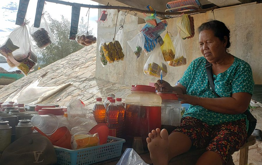 Shop owner Yang sells her wares from under a bridge after workers kicked her out from a spot along the road above, she said on December 1, 2020 in Preah Sihanouk province's Prey Nob district. (Danielle Keeton-Olsen/VOD)