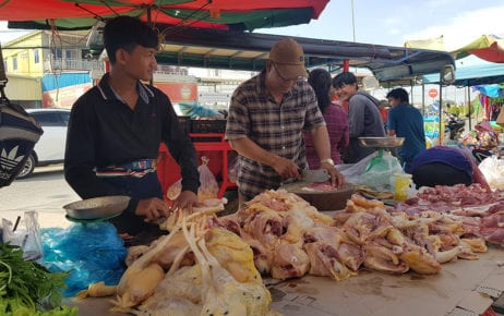 Pork seller Met Pheap (right) and chicken seller Kim Chea (left) prepare meat for sale in front of Y&W Garment Factory in Phnom Penh's Dangkor district on January 4, 2021. (Tran Techseng/VOD)