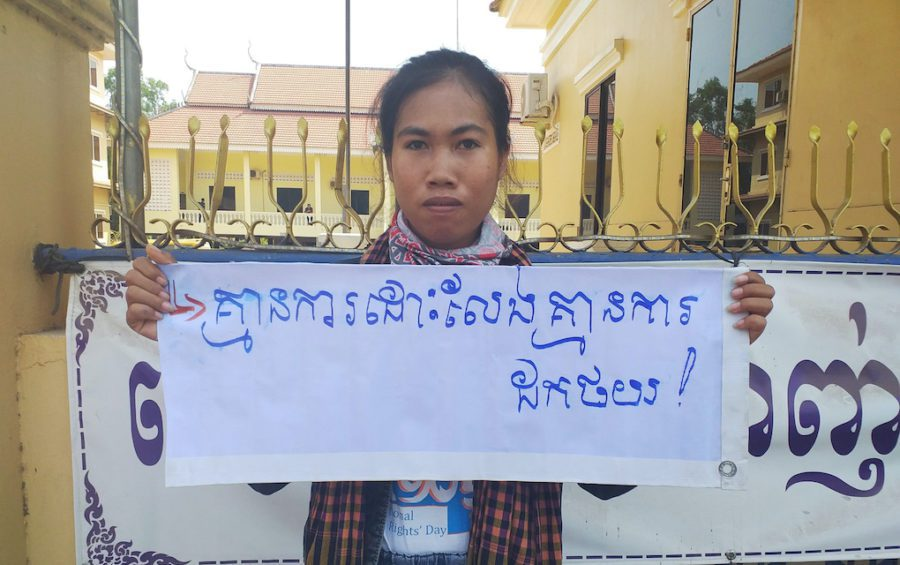 "Mother Nature Cambodia activist Long Kunthea protests the arrest of environmental activist Ouch Leng in Stung Treng province in March 2020, holding a sign reading: ""No release, no withdrawal."" (Mother Nature Cambodia)"