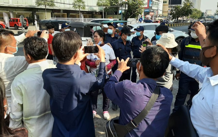 Protester Prum Chantha is surrounded by people taking photos and uniformed authorities near the Phnom Penh Municipal Court on February 4, 2021. (Va Sopheanut/VOD)