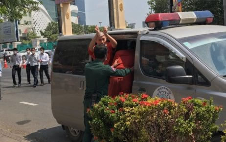 Jailed activist Chhoeun Daravy raises her handcuffed hands from a prison van after a trial hearing at the Phnom Penh Municipal Court on February 16, 2021. (Ouch Sony/VOD)