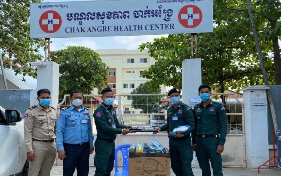 Authorities on duty at Phnom Penh's Chak Angre Health Center, where Covid-19 patients are treated, pose for a photo in February 2021 while receiving handheld metal detectors and electric-stun batons. (Phnom Penh Police Facebook)