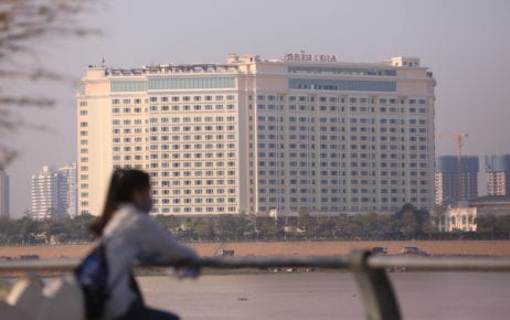 A woman wearing a mask near the Phnom Penh riverside, with the Sokha Hotel, now a Covid-19 quarantine site, seen across the river, on February 23, 2021. (Chorn Chanren/VOD)