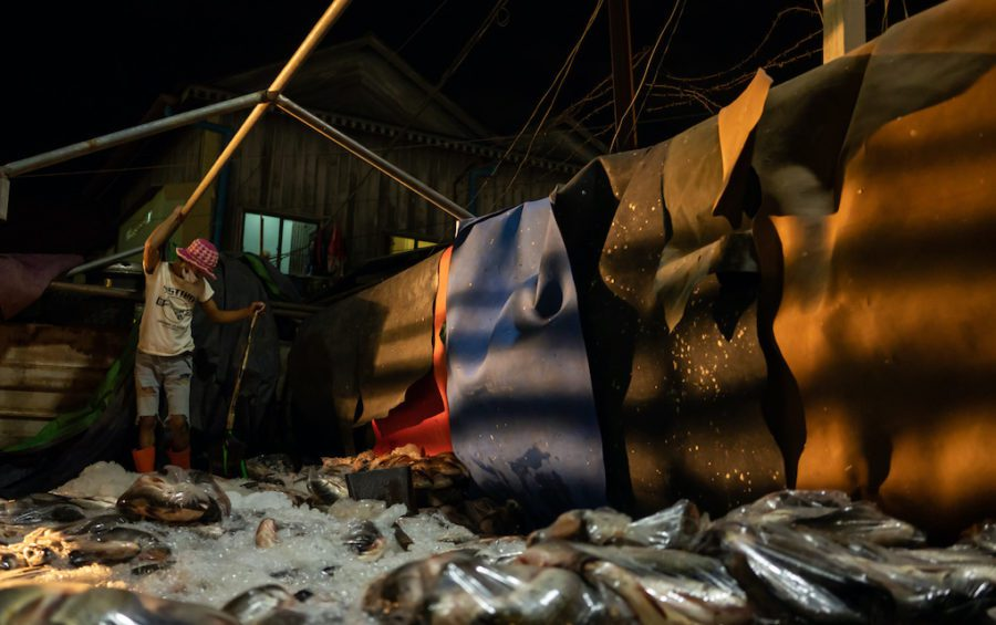 A worker offloads a truck importing fish from Vietnam to Cambodia at Phnom Penh's Prek Pnov Market. (Andy Ball)