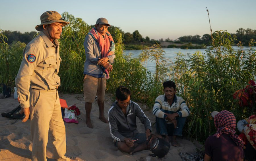 Village chief Sar Kim and community fishery patrollers discuss their patrol plans for the next 24 hours after spending a night camping on a sandbank in the Mekong while on patrol. (Andy Ball)