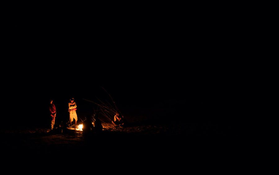 Community fishery patrollers rest around a campfire on a sandbank in the Mekong River after almost 30 hours of back-to-back patrols. (Andy Ball)