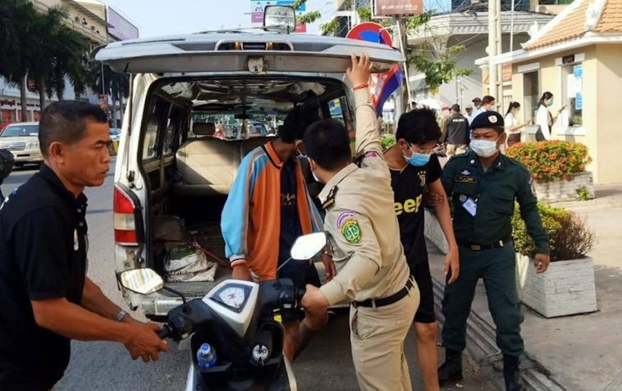 Two youths with authorities outside the Phnom Penh Municipal Court on March 10, 2021, after they were arrested for allegedly slapping a man on the back of the head. (Phnom Penh Municipal Police Facebook page)