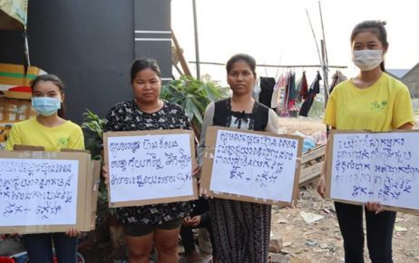 Two youth activists and two others hold signs calling for financial relief amid the Covid-19 pandemic. (Women's Association for Society)