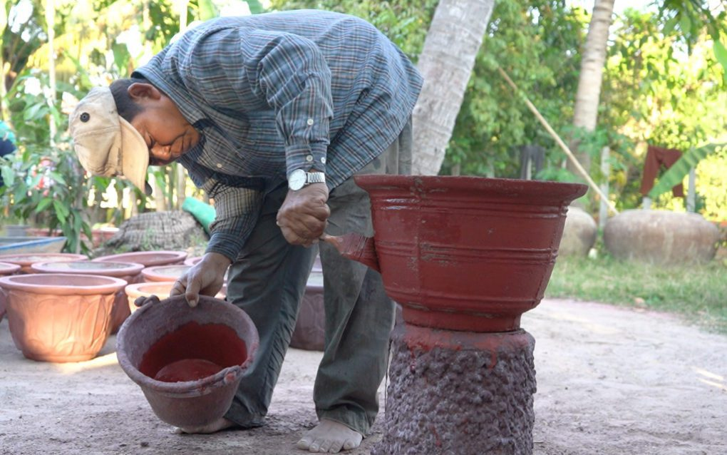 Suong Rang paints a flower pot at his home in Siem Reap province, in January 2021. (Mech Choulay/VOD)