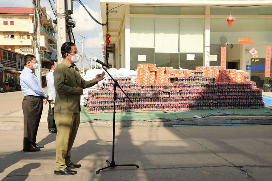 Phnom Penh governor Khuong Sreng speaks into a microphone in front of rice, soy sauce and canned fish to be distributed as emergency food aid, in a photo posted to the Phnom Penh City Hall Facebook page on April 20, 2021.