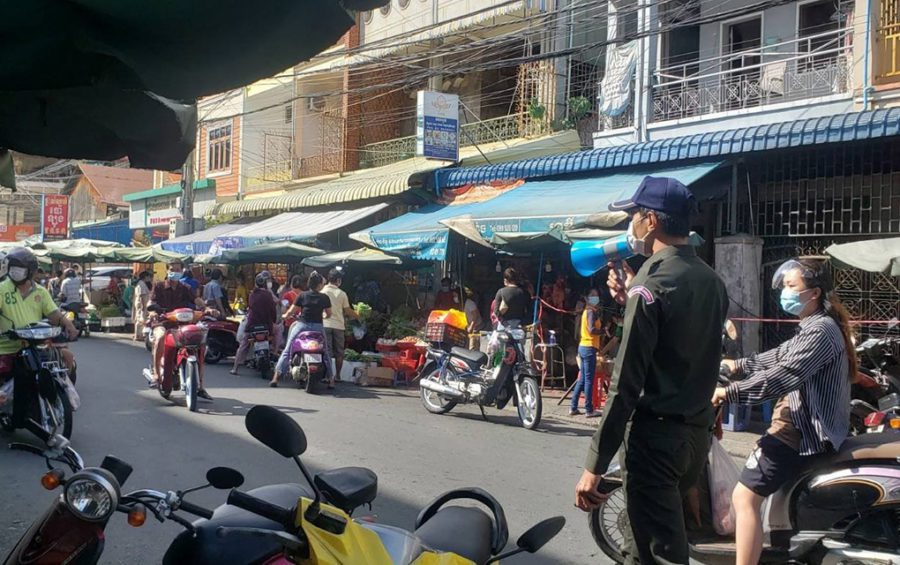 A guard talks into a loudspeaker as customers buy vegetables before a two-week market shutdown, near Phnom Penh's Olympic Market on April 24, 2021. (Danielle Keeton-Olsen/VOD)
