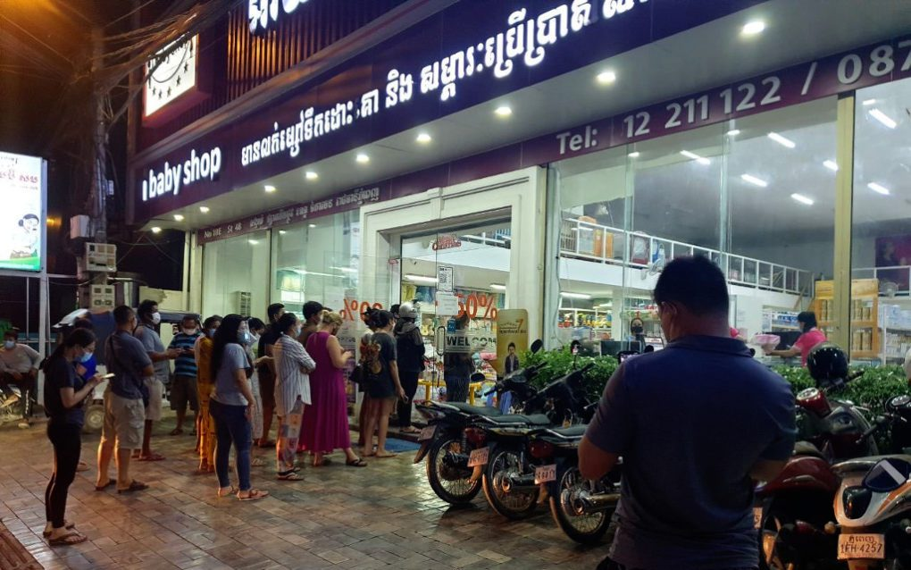 Shoppers queue outside a baby shop in Phnom Penh's Toul Tom Poung in the evening of April 14, 2021. (Mech Dara/VOD)