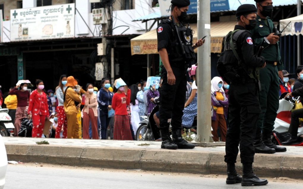Police officers stand by as Meanchey district residents protest for reduced rents on Phnom Penh's Veng Sreng Blvd. on May 10, 2021. (Michael Dickison/VOD)
