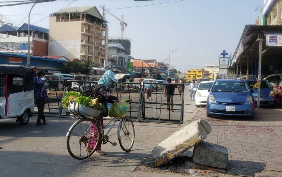 A vegetable vendor stops her bike in front of a Covid-19 restricted zone gate along Phnom Penh's Veng Sreng Blvd on May 11, 2021. (Danielle Keeton-Olsen/VOD)