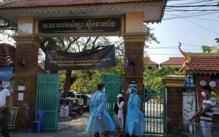 People wear personal protective equipment at the gate of the vaccine station at Phnom Penh's Stung Meanchey primary school on May 11, 2021. (Danielle Keeton-Olsen/VOD)