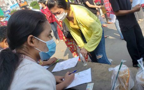 Two women fill out Covid-19 vaccine forms at the entrance to the vaccine station at Phnom Penh's Stung Meanchey primary school on May 11, 2021. (Danielle Keeton-Olsen/VOD)