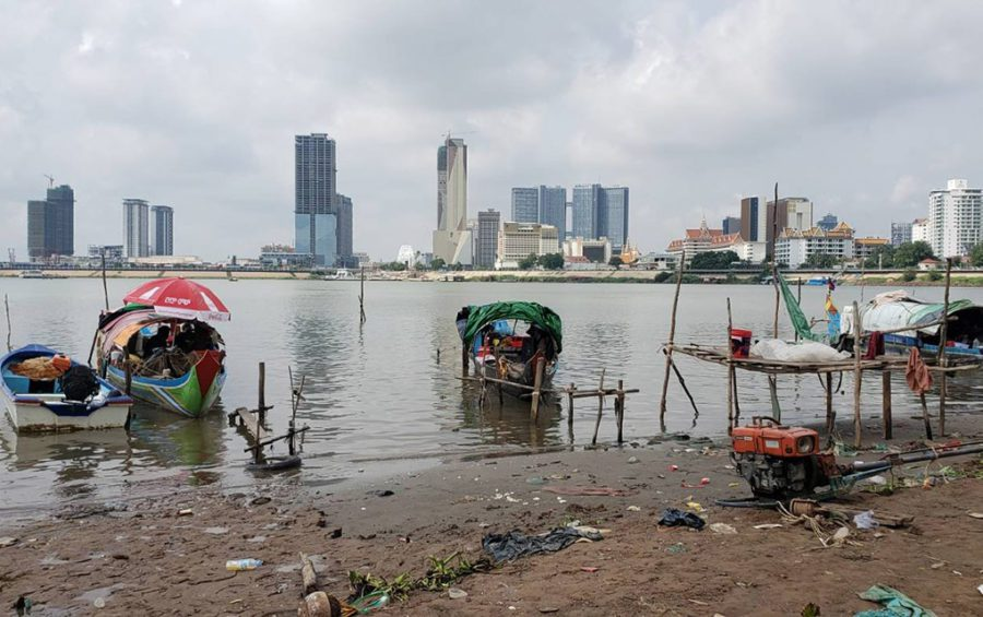 Fishing boats, which serve as homes for about 20 Cham communities, sit on the intersection of the Mekong and Sap rivers fin front of Phnom Penh's skyline on May 18, 2021. (Danielle Keeton-Olsen/VOD)