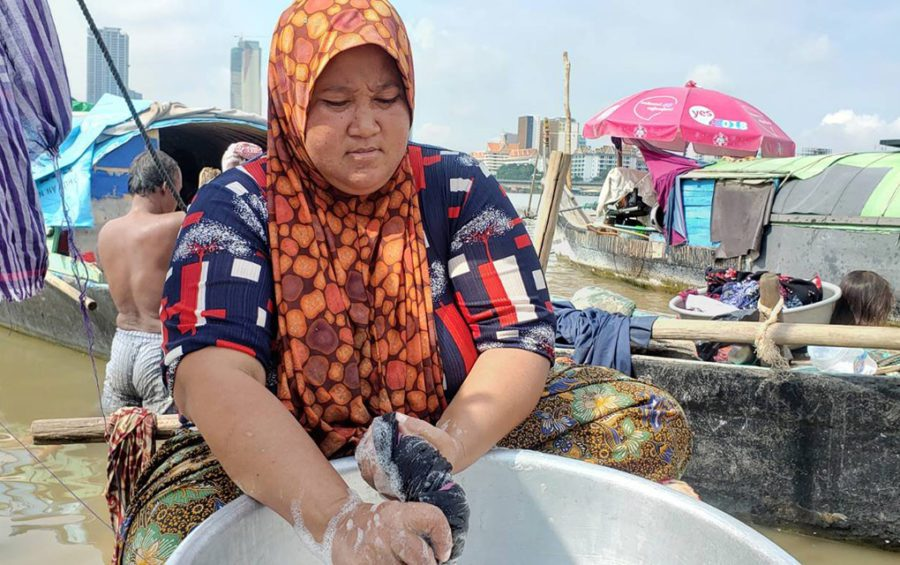 Sakiros, 40, washes her family's clothes after their boat submerged, in Phnom Penh's Chroy Changvar commune on May 18, 2021. (Danielle Keeton-Olsen/VOD)