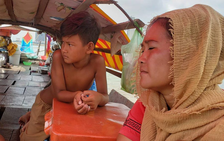 Si Fah and her son sit on their boat and home docked at Phnom Penh's Chroy Changva commune on May 18, 2021. (Danielle Keeton-Olsen/VOD)