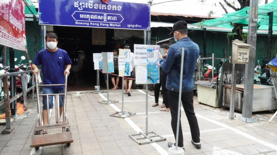 A customer at Boeng Keng Kang market scans the Stop Covid-19 QR code before entering during a limited reopening on May 24, 2021. (Tran Techseng/VOD)