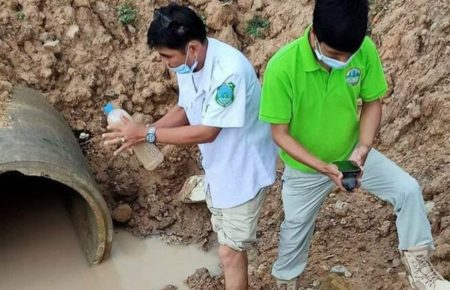 Environmental officials sample water from the Sangke river outside the Phoenix Industrial medical manufacturing plant in Battambang's Treng commune, in a photo posted to the Information Ministry website on May 26, 2021.