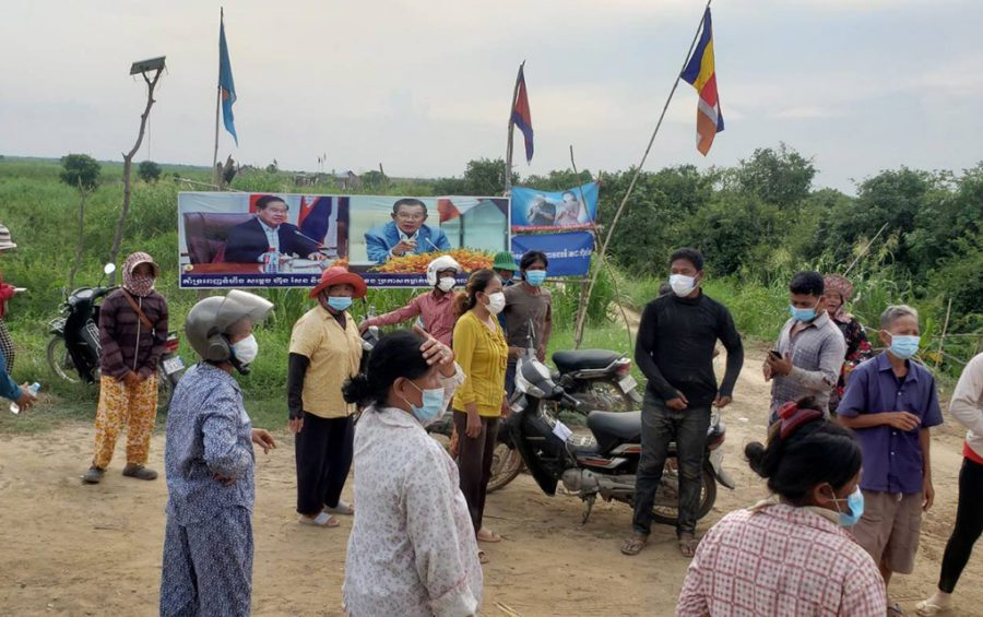 Banteay Dek commune residents gather in front of posters of Prime Minister Hun Sen and Deputy Prime Minister Sar Kheng on farmland that they say the premier awarded them in Kandal province's Kien Svay district on June 2, 2021. (Danielle Keeton-Olsen/VOD)