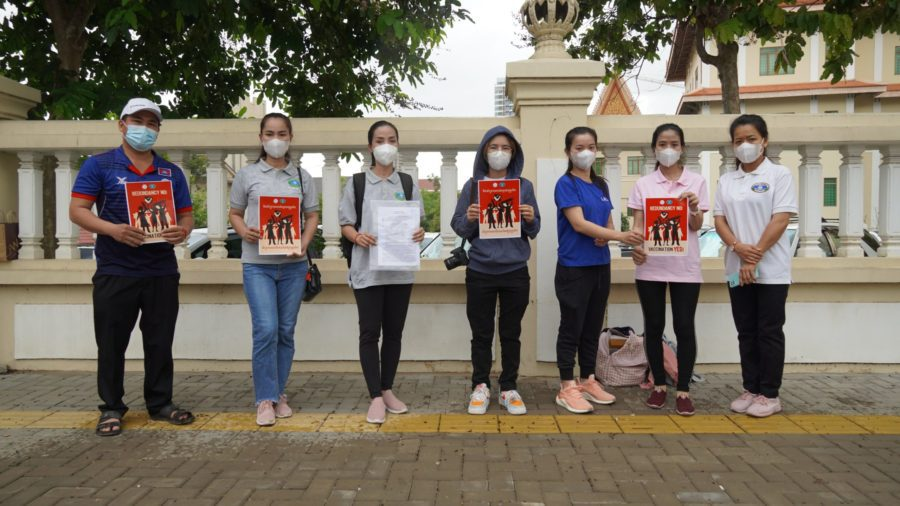Seven NagaWorld union representatives hold posters in front of the Labor Ministry gate after submitting a petition contesting the company's mass layoffs on June 8, 2021. (Tran Techseng/VOD)