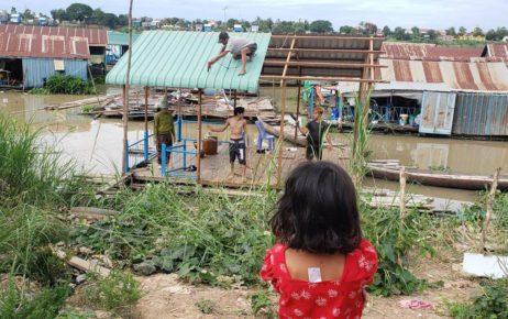 The 11-year-old daughter of Da Lin, 37, watches as volunteers dismantle their floating house in Phnom Penh's Prek Pnov village on June 10, 2021. (Danielle Keeton-Olsen/VOD)