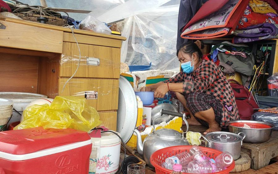 A woman, who recently dismantled her family's floating house, cooks lunch in her temporary shelter in Phnom Penh's Prek Pnov district on June 12, 2021. (Danielle Keeton-Olsen/VOD)