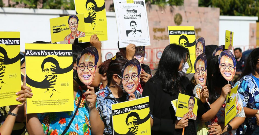 Protesters hold up face masks of Wanchalearm's likeness during a demonstration in front of the Cambodian Embassy in Bangkok on December 3, 2020 to mark six months since Wanchalearm's disappearance. (Amnesty International Thailand)