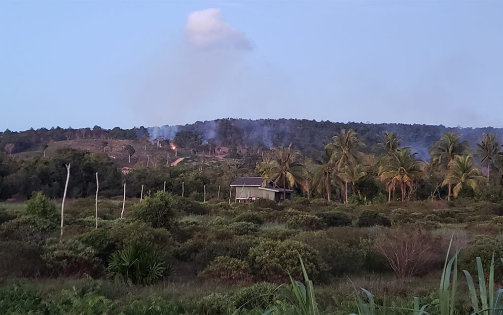 A fire burns in the hills behind the houses and land demarcation poles in Ta Chat village, part of Koh Kong province's Tuol Koki commune, on June 27, 2021. (Danielle Keeton-Olsen/VOD)