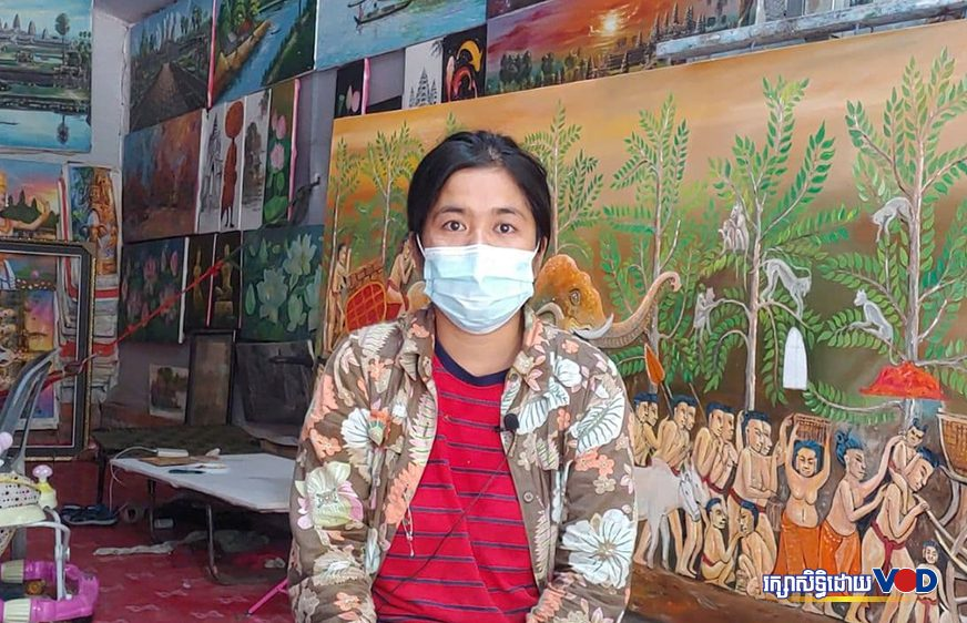 Kim Soth, an artist, wears a mask while sitting in front of her paintings in Siem Reap city's Nokor Thom commune on July 5, 2021. (Pork Kheuy/VOD)