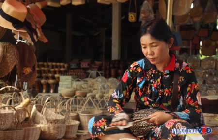 Handicraft vendor Khun Siwon polishes a wooden spoon inside her shop stocked with dozens of woven baskets in Siem Reap city's Nokor Thom commune on July 5, 2021. (Pork Kheuy/VOD)