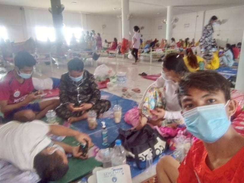 Sambath Sotherith takes a masked selfie with patients in a Covid-19 treatment center in Kampong Cham province in the background during his admission in June. (Supplied)