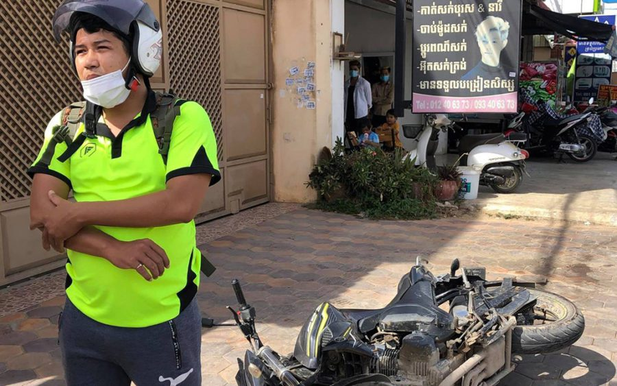 Kung Raiya stands in front of an overturned motorbike on a driveway, rubbing a scab on his elbow. (Supplied)