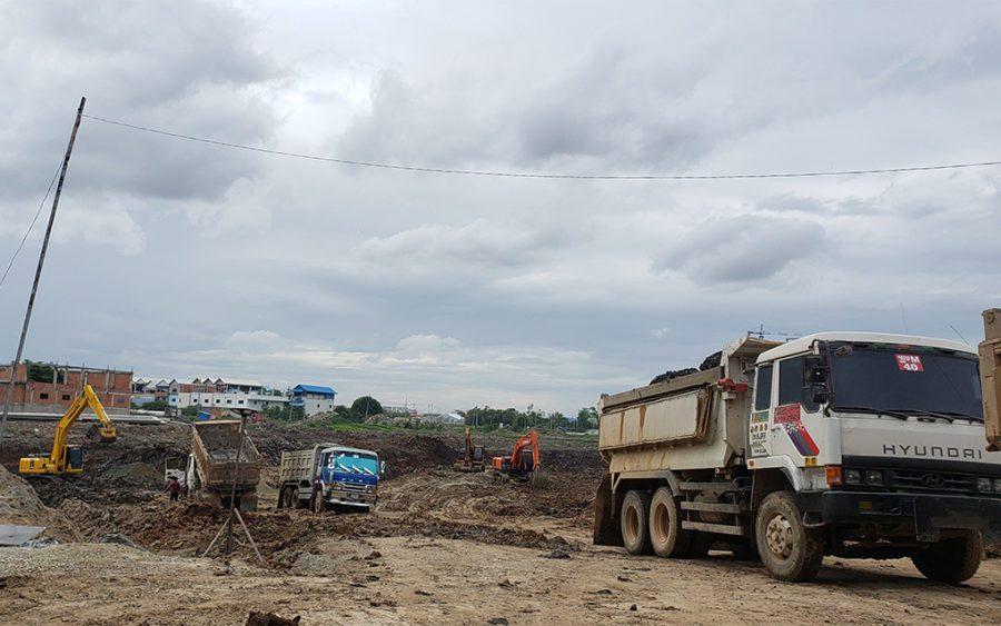 Three dump trucks and three excavators dig out the future reservoir in Boeng Tompun I commune on July 21, 2021. (Danielle Keeton-Olsen/VOD)