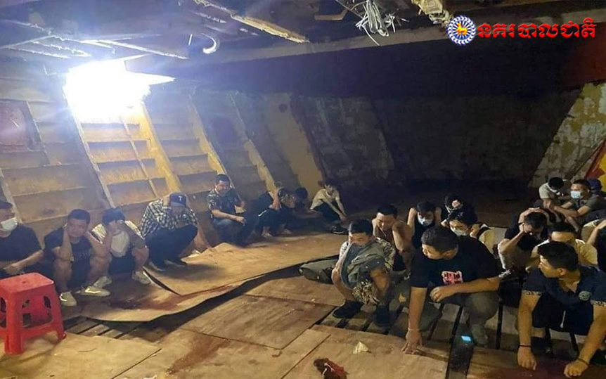 More than a dozen men crouch in the hull of a ship, which was carrying 38 Chinese and Cambodian nationals from China until stopped by authorities off the coast of Preah Sihanouk province, in a photo posted by Cambodia's National Police on July 26, 2021.