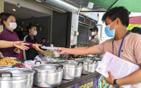 A local official hands papers explaining measures to close down dine-in at restaurants to food vendors near Phnom Penh's Phsar Kabko, on July 30, 2021. (Keat Soriththeavy/VOD)