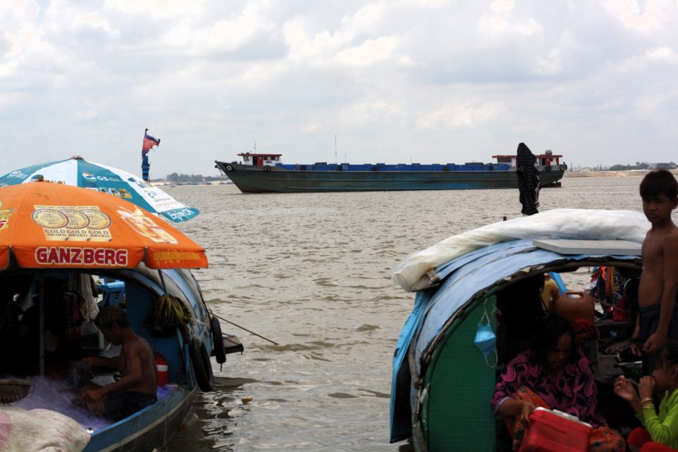 A barge passes by the shore of Phnom Penh's Chroy Changva peninsula where fishing families have moored, on July 12, 2021. (Michael Dickison/VOD)