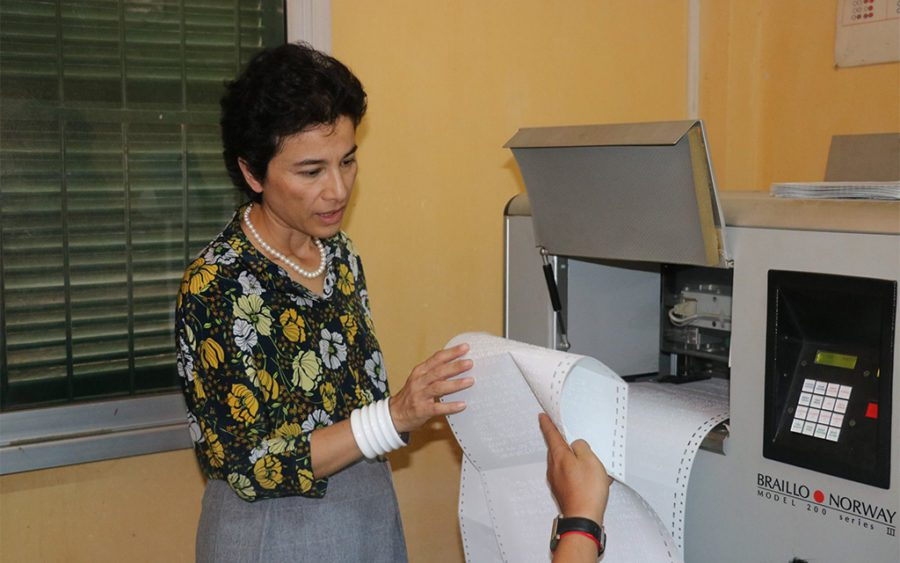 Former French Ambassador Eva Nguyen Binh examines pages printed from a Braille printer at the Institute for Special Education for Deaf and Blind Children in Phnom Penh, in a photo posted to NGO Krousar Thmey's Facebook page on July 28, 2017.