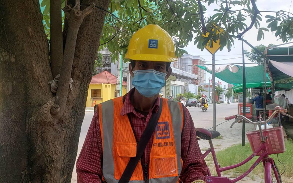 Chuon Vanny, 50, a subcontracted bricklayer wearing CSCEC gear from a previous worksite, said he's still owed money from contractors above him at the Royal Condominium construction project. (Danielle Keeton-Olsen/VOD)