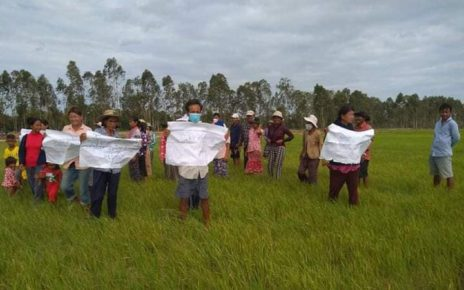 Residents, some wearing masks, stand with protest signs in a Svay Rieng rice field, in a photo posted to Yous Sophorn's Facebook page on August 4, 2021.