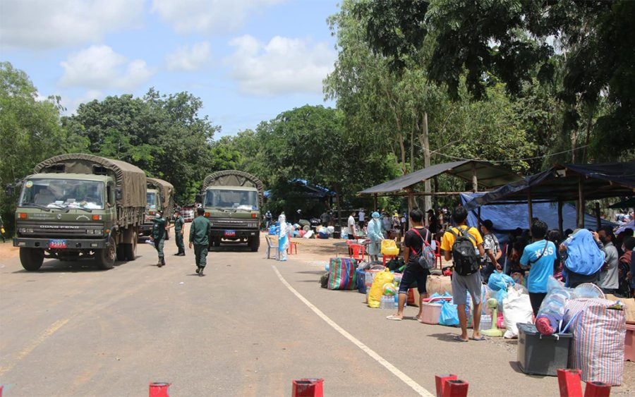 Migrant workers wait at a border checkpoint while military trucks pass in a photo posted to the Banteay Meanchey provincial administration's Facebook page on August 13, 2021.