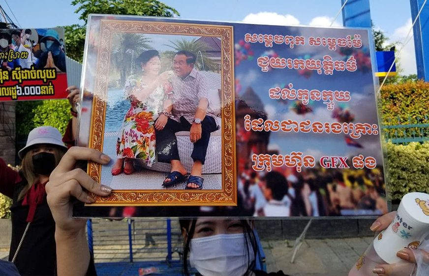 A masked protestor holds up a protest sign depicting Prime Minister Hun Sen and wife Bun Rany during a protest for compensation from the GoldFx scam at the premier's house, in a photo provided by an investor on August 16, 2021.