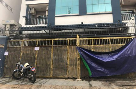 A motorbike with army plates and a tarp sit in front the gate of a condominium where military police arrested more than 100 people in Phnom Penh's Phsar Doeum Thkov commune on August 23, 2021. (Mech Dara/VOD)