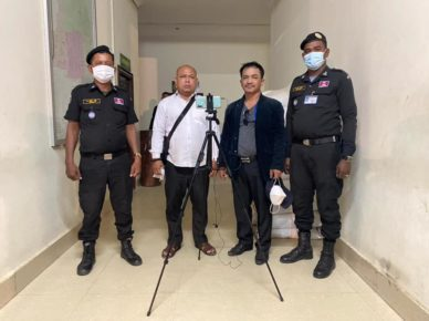 Journalists Sin Lot, 39, and Panh Phalla, 37, stand with police in a photo taken on August 30, 2021. (Provided)