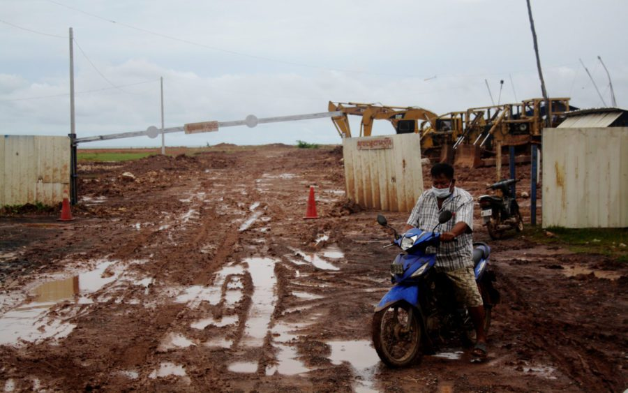 Kheav Savaong, deputy of the Kep Thmey fishing community, rides past IGB Cambodia's landfilling project in Kampot province, on August 26, 2021. (Michael Dickison/VOD)