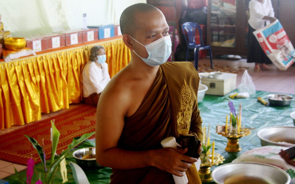 Mony Chat Tith at Phnom Penh's Wat Svay Pope wears a mask and carries disinfectant spray, on September 22, 2021. (Michael Dickison/VOD)