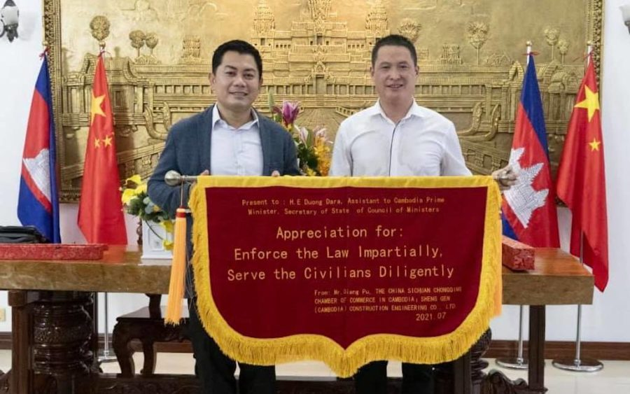 Duong Dara, left, receives a 'flag of appreciation' from a chamber of commerce, in a photo posted to his Facebook page in August 2021.